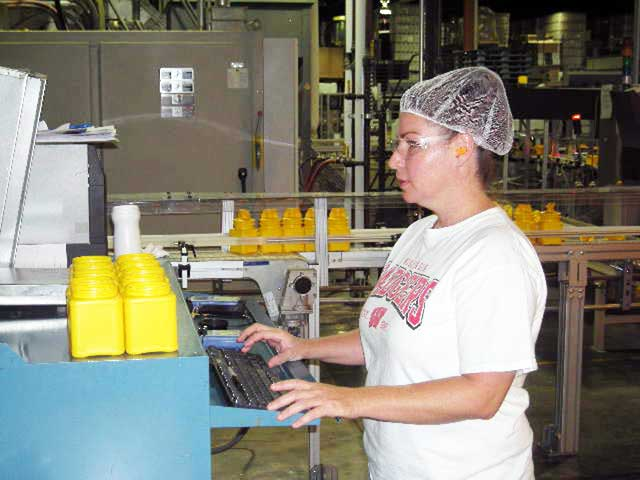 A photo of Schoeneck Containers operator using Synergy 2000 SPC software on shop floor.