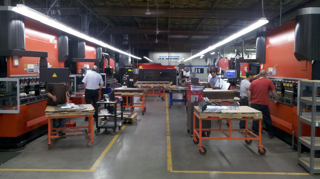 MASS Precision operators using Synergy SPC software on production floor.