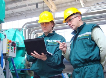 Picture of two workers consulting a screen to determine if process is in control.